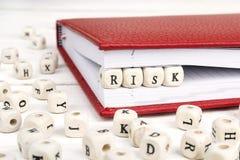 Redacte el riesgo escrito en bloques de madera en cuaderno rojo en la madera blanca Imágenes de archivo libres de regalías