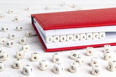 Redacte el seguro escrito en bloques de madera en cuaderno rojo en blanco Imagenes de archivo
