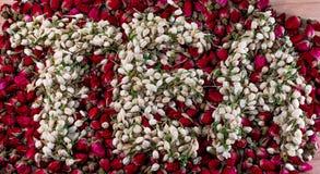Redacte el té hecho de los brotes de flor secados del jazmín sobre la pila de brotes de la rosa del rojo Foto de archivo
