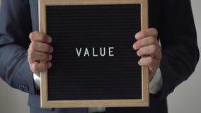 Redacte el valor de letras en tablero del texto en manos anónimas del hombre de negocios metrajes