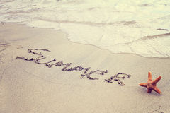 Redacte el verano escrito en arena en la playa y las estrellas de mar Vacaciones de verano, papel pintado de las vacaciones, conc Foto de archivo libre de regalías