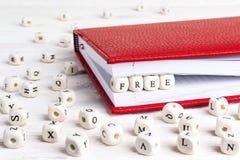 Redacte escrito libremente en bloques de madera en cuaderno rojo en la madera blanca Imagen de archivo