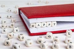 Redacte feliz escrito en bloques de madera en cuaderno rojo en blanco cortejan Foto de archivo