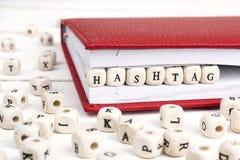 Redacte Hashtag escrito en bloques de madera en cuaderno rojo en la tabla de madera blanca Foto de archivo