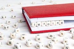 Redacte Imagine escrita en bloques de madera en cuaderno rojo en w blanco Imágenes de archivo libres de regalías