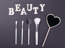 Redacte la belleza al lado de los accesorios para el maquillaje en fondo negro Imagen de archivo