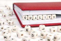 Redacte la calidad escrita en bloques de madera en cuaderno rojo en w blanco Fotografía de archivo libre de regalías
