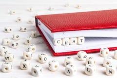 Redacte la charla escrita en bloques de madera en cuaderno rojo en la madera blanca Imagenes de archivo