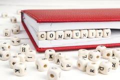 Redacte a la comunidad escrita en bloques de madera en cuaderno rojo en blanco Fotografía de archivo