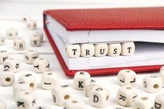 Redacte la confianza escrita en bloques de madera en cuaderno rojo en blanco cortejan Imagenes de archivo