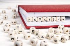 Redacte la donación escrita en bloques de madera en cuaderno rojo en blanco Fotos de archivo
