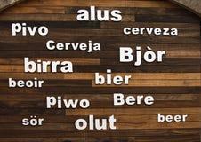 Redacte la escritura del ` de la cerveza del ` en la pared de madera en otros idiomas imagen de archivo libre de regalías