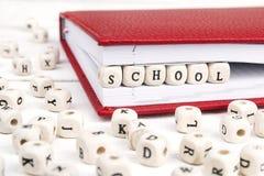 Redacte la escuela escrita en bloques de madera en cuaderno rojo en el wo blanco Imagen de archivo