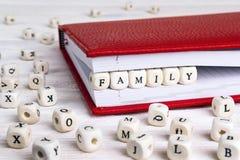 Redacte a la familia escrita en bloques de madera en cuaderno rojo en el wo blanco Fotos de archivo