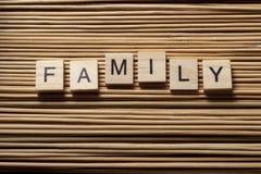 Redacte a la FAMILIA escrita en los cubos de madera en el fondo de madera Foto de archivo libre de regalías