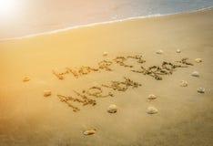 Redacte la Feliz Año Nuevo en la arena de la playa Foto de archivo libre de regalías