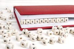 Redacte la instrucción escrita en bloques de madera en cuaderno rojo en whi Fotografía de archivo libre de regalías