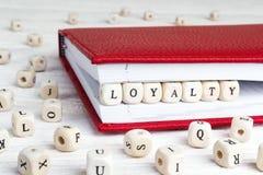 Redacte la lealtad escrita en bloques de madera en cuaderno rojo en w blanco fotografía de archivo libre de regalías