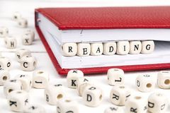 Redacte la lectura escrita en bloques de madera en cuaderno rojo en w blanco Fotografía de archivo libre de regalías
