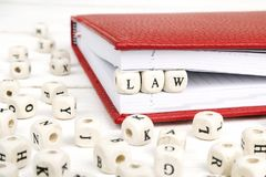 Redacte la ley escrita en bloques de madera en cuaderno rojo en el woode blanco Foto de archivo