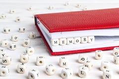 Redacte la memoria escrita en bloques de madera en cuaderno rojo en el wo blanco Fotos de archivo libres de regalías