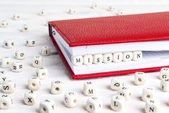 Redacte la misión escrita en bloques de madera en cuaderno rojo en w blanco Imágenes de archivo libres de regalías