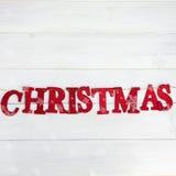 Redacte la Navidad hecha de las letras que brillan rojas puestas en el St Foto de archivo libre de regalías
