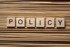 Redacte la POLÍTICA en los cubos de madera del ABC en el fondo de madera Foto de archivo