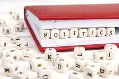 Redacte la política escrita en bloques de madera en cuaderno rojo en blanco Fotografía de archivo