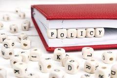 Redacte la política escrita en bloques de madera en cuaderno rojo en el wo blanco Imagenes de archivo