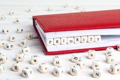 Redacte la prioridad escrita en bloques de madera en cuaderno rojo en blanco Foto de archivo libre de regalías