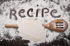 Redacte la receta escrita en la harina blanca y la espátula en la madera Foto de archivo libre de regalías