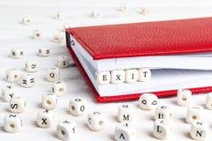Redacte la salida escrita en bloques de madera en cuaderno rojo en la madera blanca Fotografía de archivo