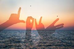 Redacte la silueta del amor de dos personas jovenes que hacen la forma del amor de manos en la playa en el tiempo de verano del c Imagen de archivo