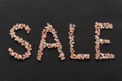 Redacte la venta escrita en cristales rosados de la sal de Hymalayan en backgr negro Imágenes de archivo libres de regalías