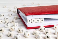 Redacte la yoga escrita en bloques de madera en cuaderno rojo en la madera blanca Foto de archivo