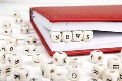 Redacte las noticias escritas en bloques de madera en cuaderno rojo en la madera blanca Imagen de archivo libre de regalías