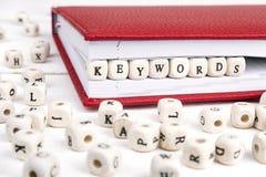 Redacte las palabras claves escritas en bloques de madera en cuaderno rojo en blanco Imagenes de archivo