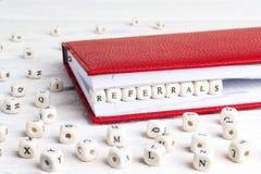 Redacte las remisiones escritas en bloques de madera en cuaderno rojo en blanco Imagen de archivo libre de regalías