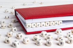 Redacte las vacaciones escritas en bloques de madera en cuaderno rojo en blanco Imagen de archivo libre de regalías