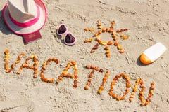 Redacte las vacaciones, los accesorios para tomar el sol y el pasaporte en la arena en la playa, concepto del tiempo de verano Imágenes de archivo libres de regalías