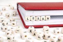 Redacte Learn escrito en bloques de madera en cuaderno rojo en blanco cortejan Fotografía de archivo