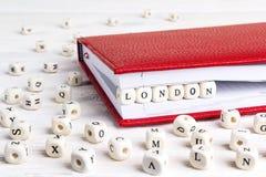 Redacte Londres escrito en bloques de madera en cuaderno rojo en el wo blanco Fotos de archivo libres de regalías