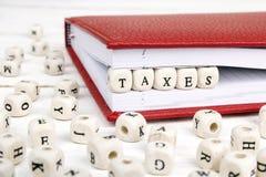Redacte los impuestos escritos en bloques de madera en cuaderno rojo en blanco cortejan Imagen de archivo
