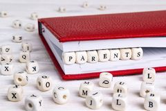 Redacte a los padres escritos en bloques de madera en cuaderno rojo en w blanco Imagen de archivo