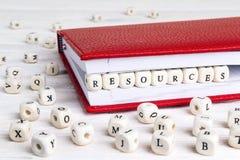 Redacte los recursos escritos en bloques de madera en cuaderno rojo en blanco Fotografía de archivo libre de regalías