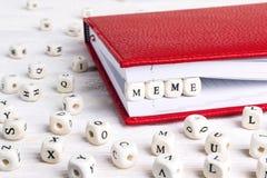 Redacte Meme escrito en bloques de madera en cuaderno rojo en la madera blanca Fotos de archivo libres de regalías