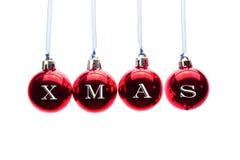 Redacte Navidad en las bolas rojas de la Navidad que cuelgan en el fondo blanco Fotos de archivo libres de regalías