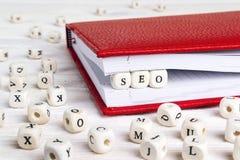 Redacte SEO escrito en bloques de madera en cuaderno rojo en el woode blanco Imagen de archivo