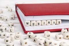 Redacte Webinar escrito en bloques de madera en cuaderno rojo en w blanco Imagenes de archivo